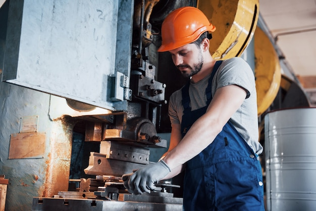 Portrait of a young worker in a hard hat at a large metalworking plant