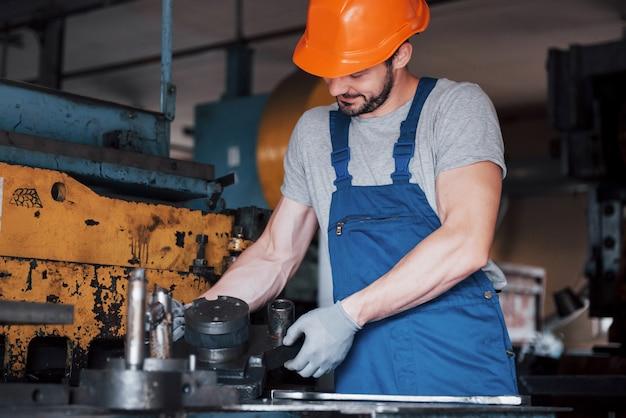Ritratto di un giovane operaio in un cappello duro in un grande impianto di lavorazione dei metalli.