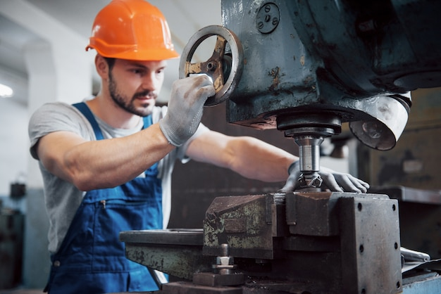 Portrait of a young worker in a hard hat at a large metalworking plant.