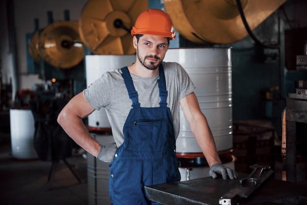 Ritratto di un giovane operaio in un elmetto in una grande fabbrica di riciclaggio dei rifiuti.