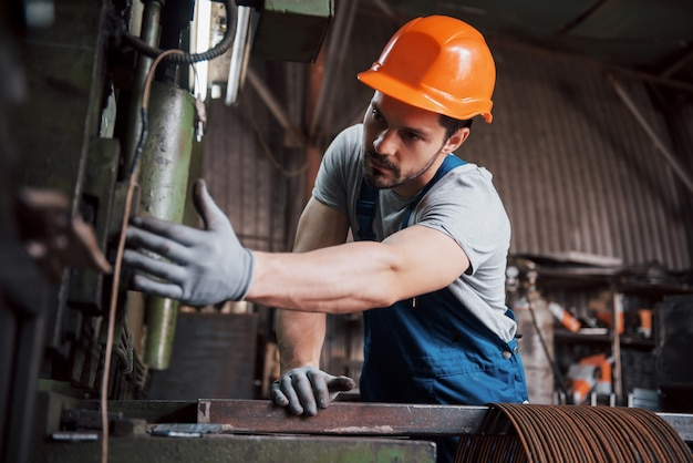 Portrait of a young worker in a hard hat at a large waste recycling factory.