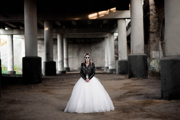 Portrait of zombie woman with painted skull face under a bridge.