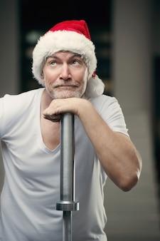 ジムの大晦日とクリスマスのコンセプトでサンタクロースの帽子の年配の男性の肖像画