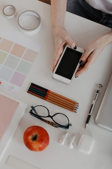 Portraitgraph of office stationery on white and female hands with black manicure, holding smartphone.