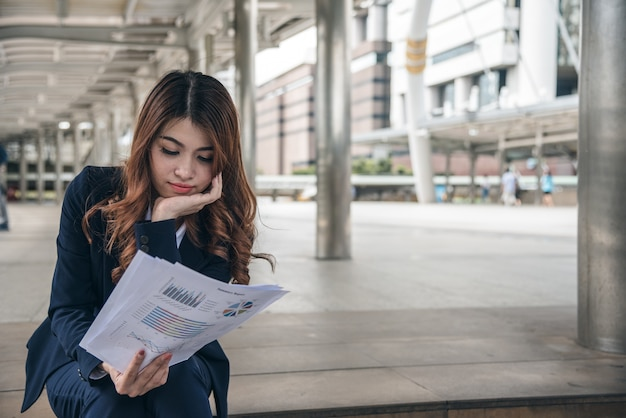 Portraits of beautiful asian woman in thinking expression working with financial chart document