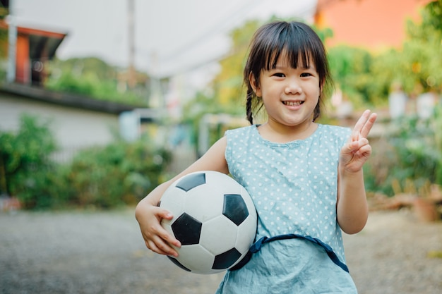 Portraits of a kids enjoy playing soccer football for exercise.