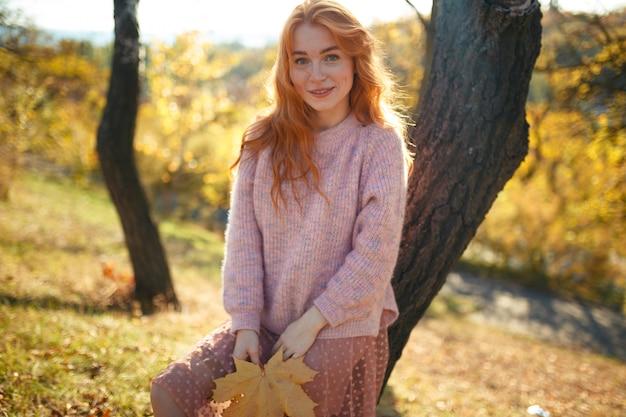 Портреты очаровательной рыжеволосой девушки с симпатичным лицом. девушка позирует в осенний парк в свитер и коралловые юбки. в руках у девушки желтый лист