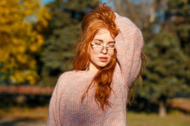 Портреты очаровательной рыжеволосой девушки с симпатичным лицом. девушка позирует в осенний парк в свитер и коралловые юбки. у девушки прекрасное настроение
