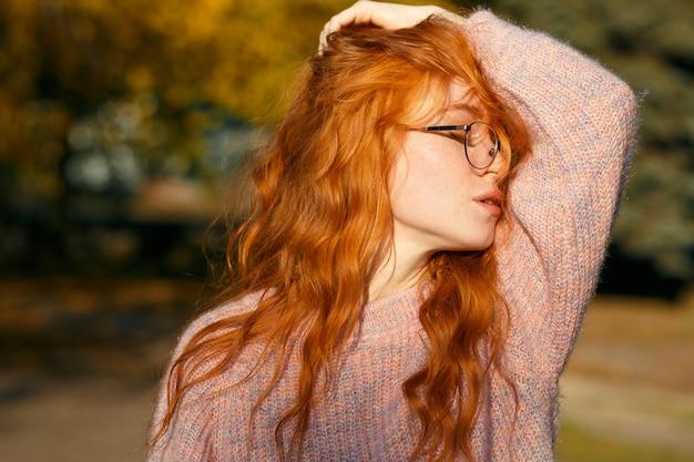 Портреты очаровательной рыжеволосой девушки с очками и милым лицом. девушка позирует в осенний парк в свитер и коралловые юбки. у девушки прекрасное настроение