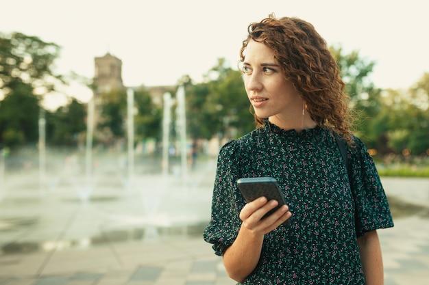 Портреты очаровательной рыжеволосой девушки с симпатичным лицом. девушка держит в руках мобильный телефон и смотрит в сторону. у нее отличное настроение и милая улыбка