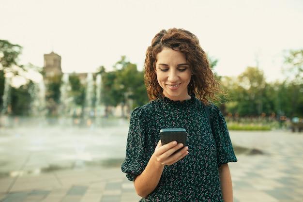 Портреты очаровательной рыжеволосой девушки с симпатичным лицом. девушка смотрит на свой телефон. у нее отличное настроение и милая улыбка