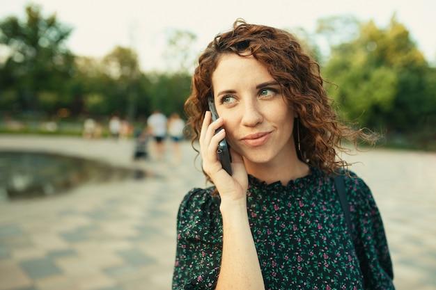 Портреты очаровательной рыжеволосой девушки с симпатичным лицом. девушка мило разговаривает с кем-то по телефону. у нее отличное настроение и милая улыбка