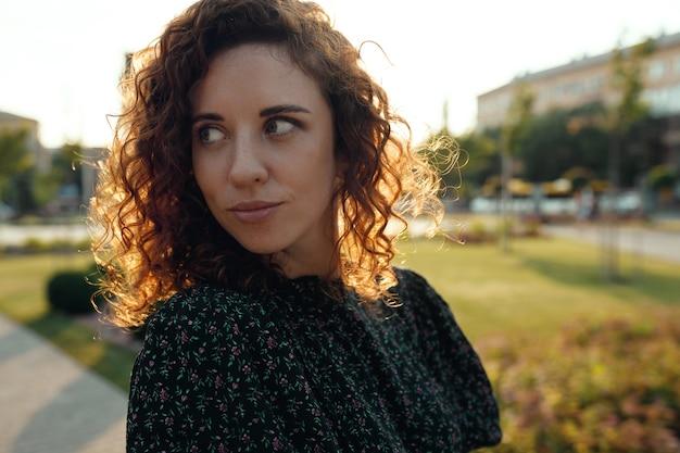 Портреты очаровательной рыжеволосой девушки с веснушками и симпатичным личиком. девушка позирует на камеру в центре города. у нее отличное настроение и милая улыбка