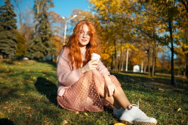 Портреты очаровательной рыжеволосой девушки в очках и с красивым лицом. девушка позирует в осенний парк в свитер и юбка кораллового цвета.