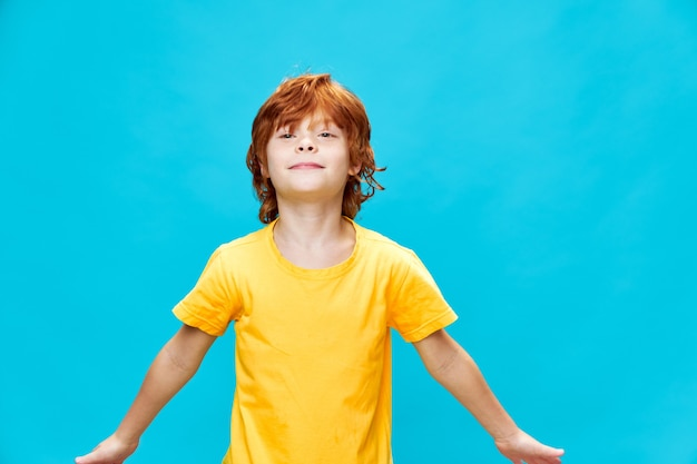 黄色のtシャツを着た赤い髪の少年の肖像画が両手を横に投げます