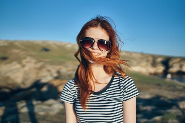 山の青い空夏の太陽の冒険の川の近くの赤毛の旅行者の肖像画