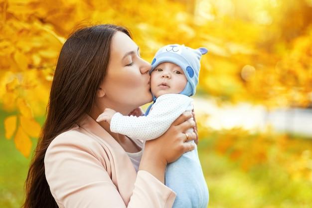 秋の公園でママと赤ちゃんの肖像画、ママは赤ちゃんを抱きしめてキスします
