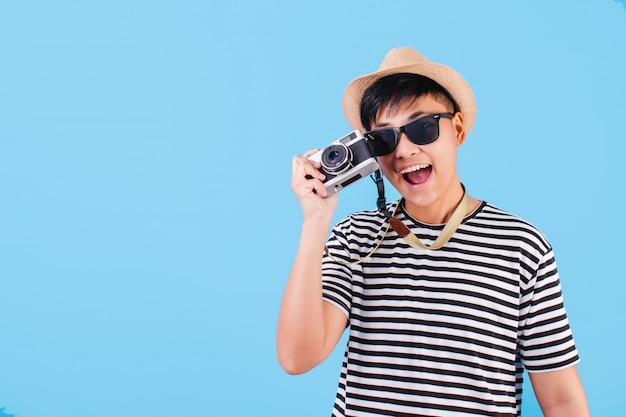 黒と白のストライプのシャツを着て、フィルムカメラを持って幸せな観光客の肖像画。孤立した青