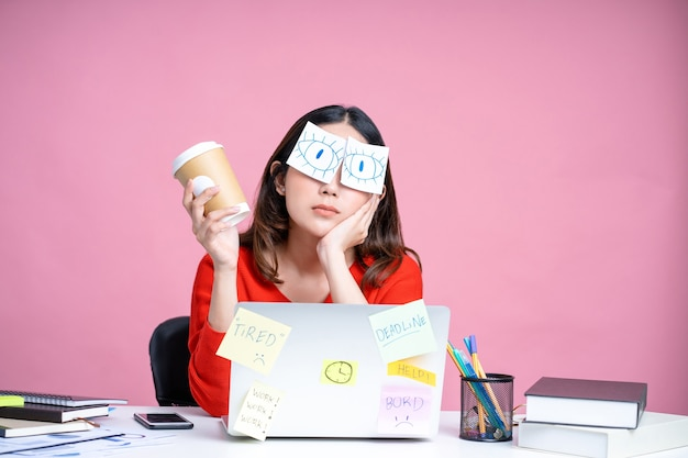 Portraits of overworked asian women. she was sitting at her desk with stickers covering her eyes and using her laptop on a pastel pink background.