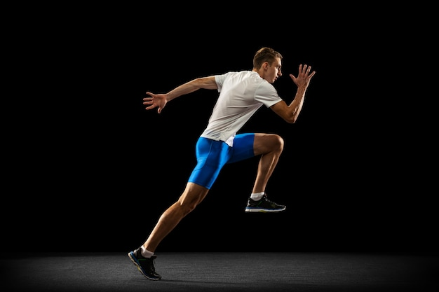 Portrat of caucasian professional male athlete, runner training isolated on black
