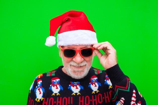 Портрет пожилого и зрелого мужчины, улыбающегося и смотрящего в камеру в рождественской одежде - празднование рождества