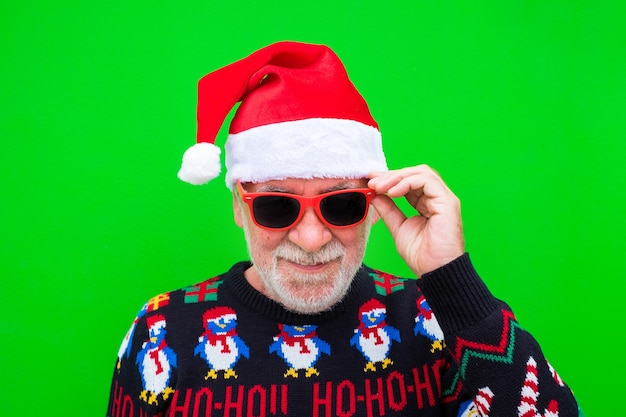 Portrat of old and mature man smiling and looking at the camera wearing christmas clothes  - celebrating xmas