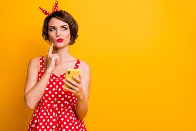 Портрет мыслящей задумчивой девушки-блогера хочет набрать текст сообщения в чате думать мысли выглядят copyspace прикосновение пальца подбородок носить одежду в стиле ретро, изолированную над яркой цветной стеной