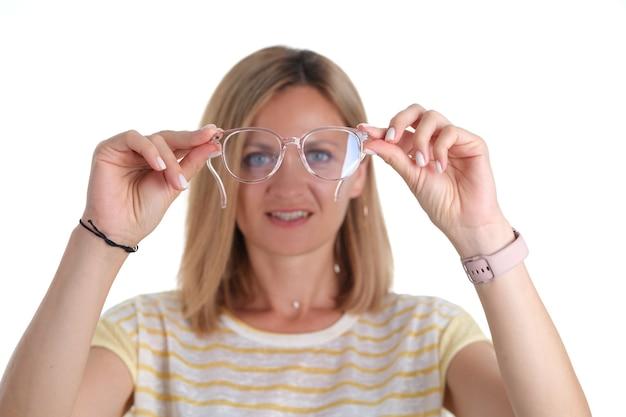 Портрет молодой женщины с плохим зрением держит в руках очки