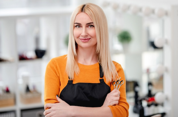 Portret of blond woman hairdresser smiling and holding in her hand scissors