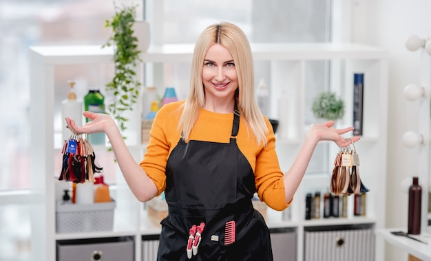 彼女の手で染毛のためのカラフルなサンプルを保持しているサロンの美容師の肖像画