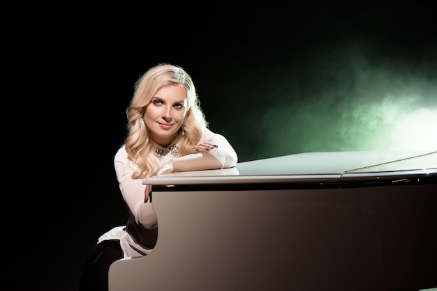 Портрет пианиста позирует возле белого рояля на сцене в луче света.