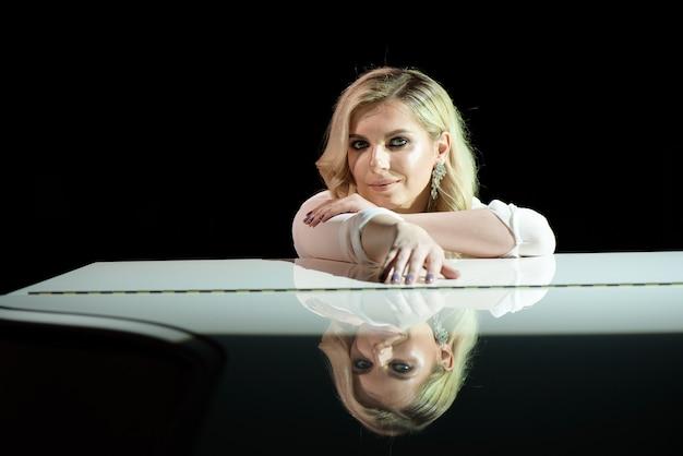 Портрет пианиста позирует возле белого пианино на сцене в луче света.