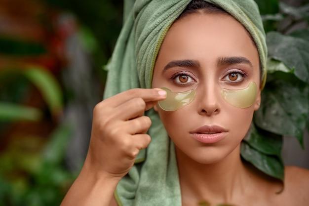 Портретное фото роскошной кареглазой женщины, которая убирает пятна с глаз.