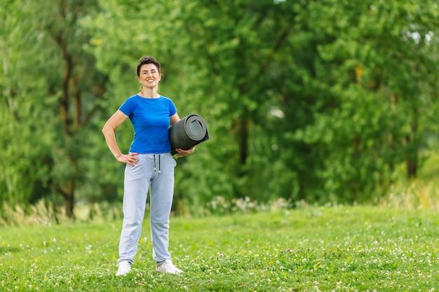 Portret старшей женщины работая в парке.