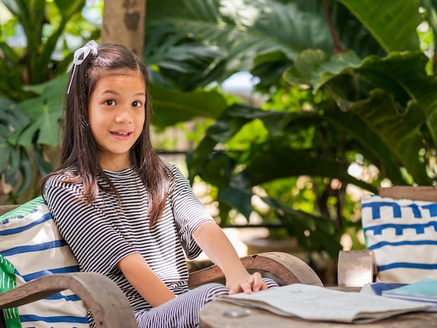 Portriat image of 8 years old asian girl reading or doing homework at her backyardschool kid in holiday in the garden