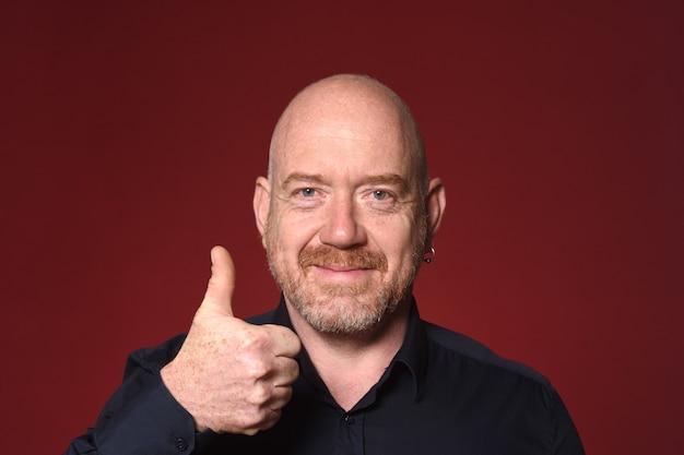 Portriat человека с большими пальцами руки вверх на красном фоне