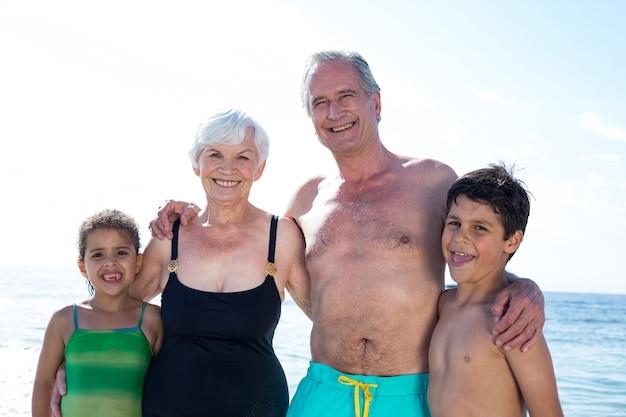 Portriat бабушки и дедушки с внуками на пляже