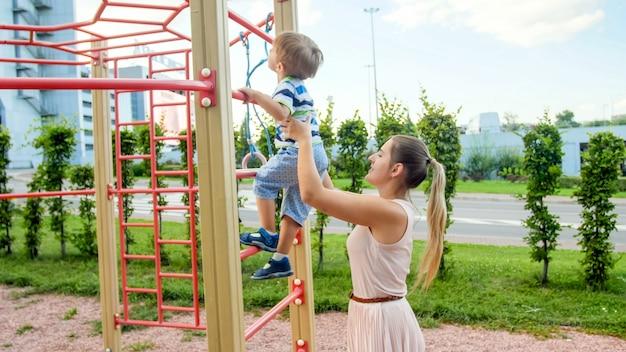 공원에서 어린이 놀이터에서 금속 사다리에 그녀의 3 살짜리 아이 아들을 지원하고 잡고있는 젊은 어머니의 portriat