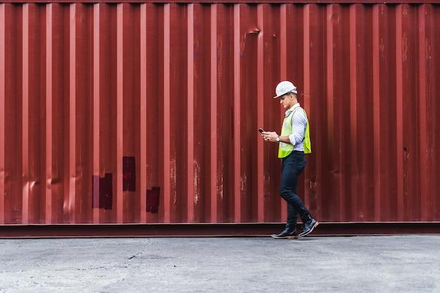 Инженер-работник portrit идет к проверке коробки контейнеров с грузового корабля на экспорт и импорт