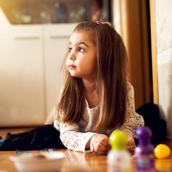 素敵な絵を描いて、床に横になっている美しい少女のportrsit