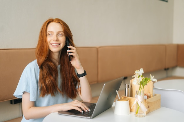 Portrtait of happy young woman talking on smartphone and using laptop sitting at table by window in cozy light cafe, looking away. pretty redhead caucasian lady remote working or studying.