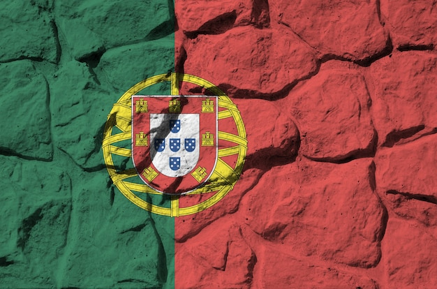 Portugal flag depicted in paint colors on old stone wall closeup. textured banner on rock wall background
