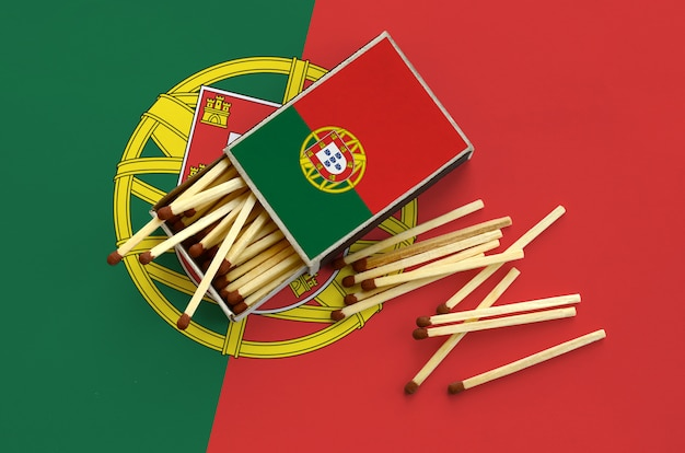 Portugal flag  is shown on an open matchbox, from which several matches fall and lies on a large flag