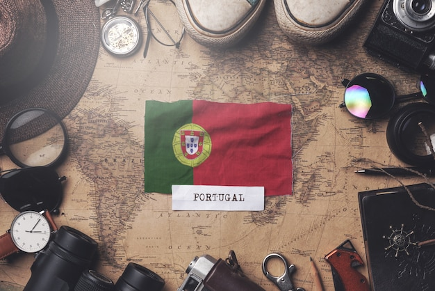 Portugal flag between traveler's accessories on old vintage map. overhead shot