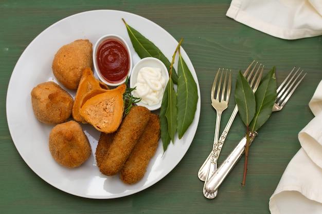 Португальские закуски с соусами на белой тарелке на зеленом