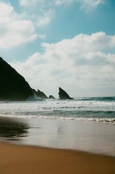 ポルトガルのビーチ、海岸線、海岸、冬の間の海の景色。プライアダアドラガ、シントラ海岸線。曇りの冬の日。波に選択的に焦点を当てます。