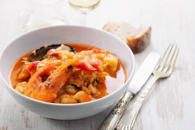 Тушеная рыба и морепродукты по-португальски в блюде на керамической поверхности