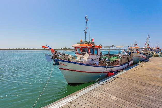 Португальская рыбацкая лодка на пирсе. с традиционными цветами.