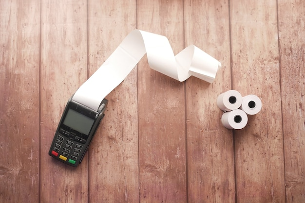 Pos machine and long roll paper on table