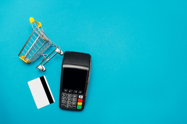 Pos payment terminal with credit card and supermarket trolley on blue background. shopping online and sale concept.